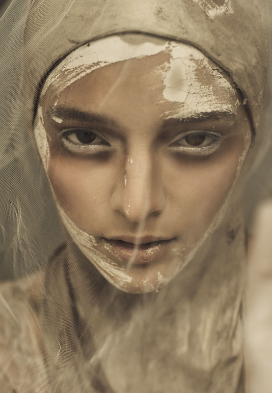 Female model under veil and covered with wet clay and makeup by Nika Vaughan