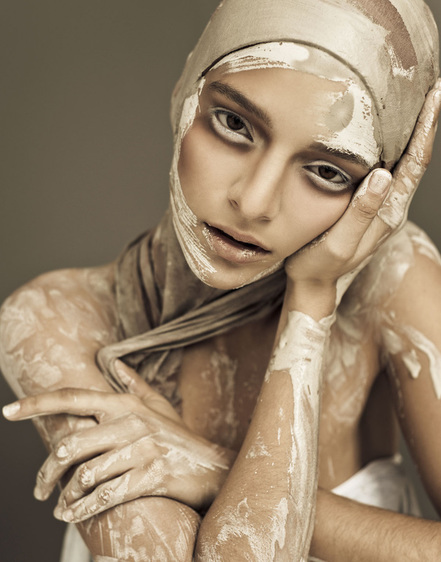 Female model covered in wet clay and makeup by Nika Vaughan